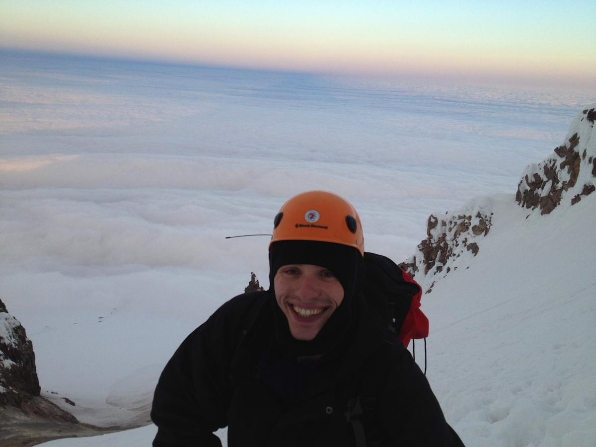 Rodney's photo looking west on top of Mount Hood with Steve smiling and clouds below