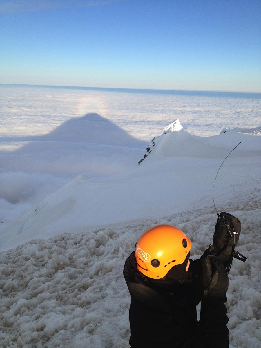 Rodney's photo of KB3QEW operating with Yaesu VX-8GR on Mount Hood summit in the sun looking west